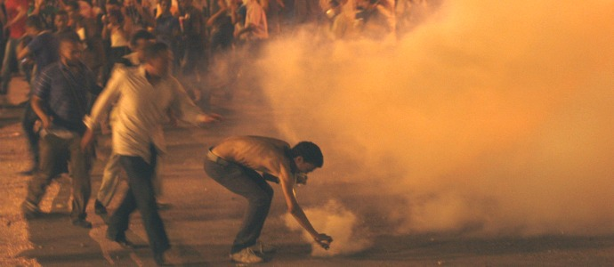 In this June 29, 2011 file photo, demonstrators throw a tear gas grenade during clashes with the Egyptian security in Tahrir Square in Cairo, Egypt. What appeared an unstoppable groundswell for change across the Middle East earlier this year, has splintered into scattered and indecisive conflicts that have left thousands dead and Western policy makers juggling roles ranging from NATO airstrikes in Libya to worried bystanders in Syria and Yemen.(AP Photo/Khalil Hamra, File)