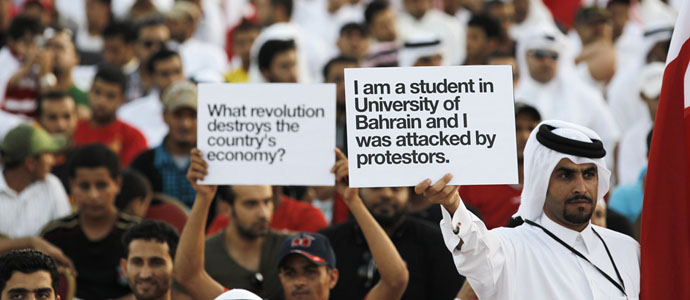 Pro-government supporters hold banners at a rally held in Riffa, south of Manama