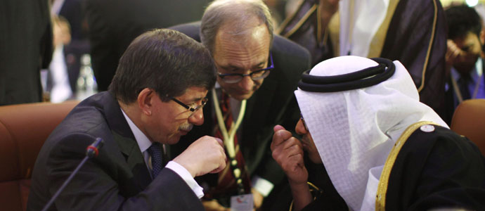 Turkey's Foreign Minister Ahmet Davutoglu confers with United Arab Emirates' Foreign Minister Sheikh Abdullah bin Zayed al-Nahyan during the Friends of Syria Conference in Tunis