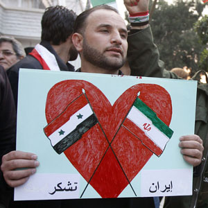 "A pro-Assad protester holds a sign showing the Syrian and Iranian flags with Arabic words reading ""Thanks Iran"" during a protest in Damascus, Syria, November 24, 2011 (AP photo)."
