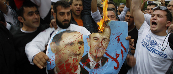 Syrian protesters shout slogans as they burn a poster of Syrian President Bashar Assad, left, and his father Hafez Assad during a demonstration in front of the Syrian embassy, in Nicosia, Cyprus Friday, April 22, 2011. Several hundred Syria protesters resident in Cyprus, called for Syrian President Bashar Assad's ouster.