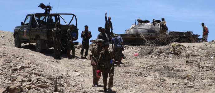 Army soldiers stand at a mountain military position near the southern Yemeni city of Lawdar