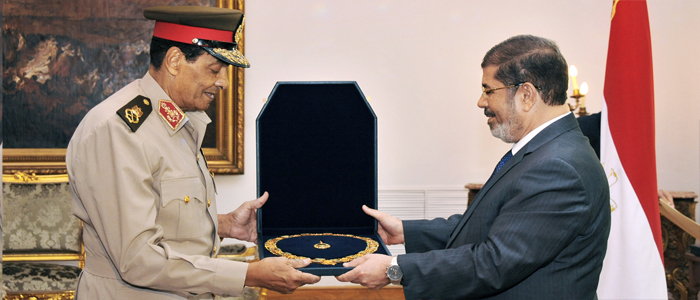 Former Defense Minister Hussein Tantawi, left, receives a high medal from Egyptian President Mohammed Morsi at the Presidential Palace in Cairo, Egypt, Tuesday, Aug. 14, 2012. (AP Photo/Middle East News Agency)