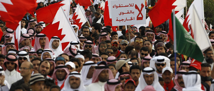 Pro-government protesters hold Bahraini flags and a banner as they participate in a pro-government rally held in al Fateh Grand Mosque in Manama