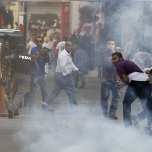Protesters and a reporter run to take cover from tear gas fired by riot police during an anti-government march in Manama September 7, 2012.