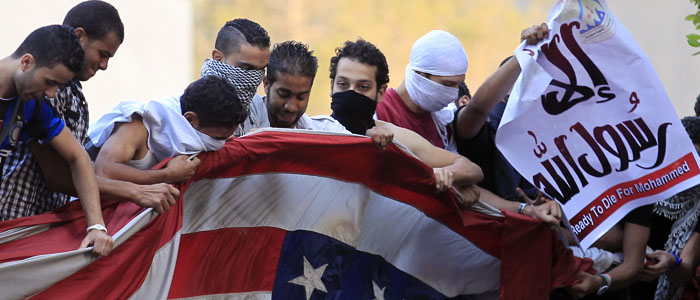 Protesters destroy an American flag pulled down from the U.S. embassy in Cairo
