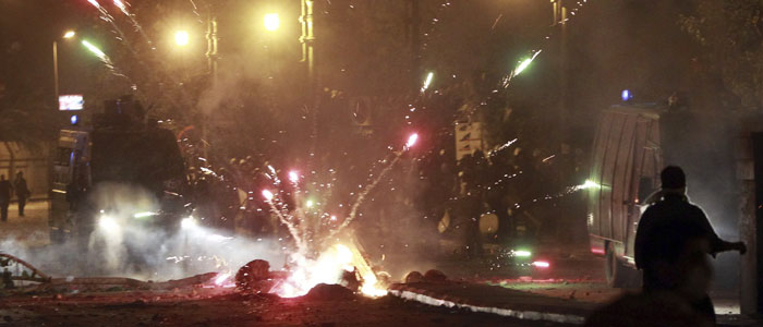 Fireworks explode as protesters clash with riot police along a road at Kornish El Nile which leads to the U.S. embassy, near Tahrir Square in Cairo