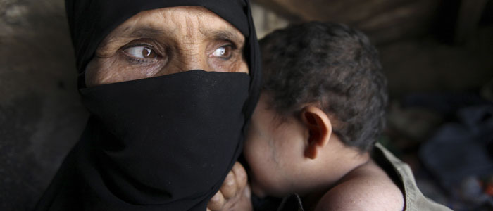 A woman holds her child in their home in Sanaa