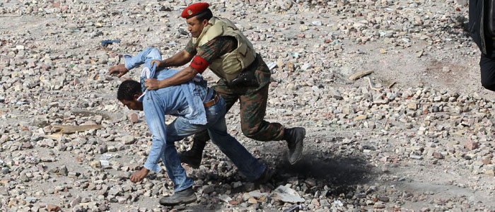 Supporter of Egyptian President Hosni Mubarak is taken to the ground by a soldier in Cairo
