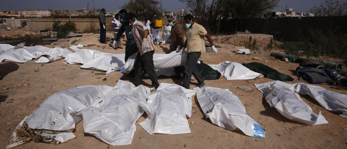 Volunteers carry a body as they try to identify 26 exhumed bodies found in unknown graves that were buried during the conflict between rebel fighters and forces loyal to Muammar Gaddafi, in Sirte