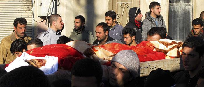 Men carry the body during a funeral of one of the five civilians killed during a Syrian Army bombardment on Al Qusayr