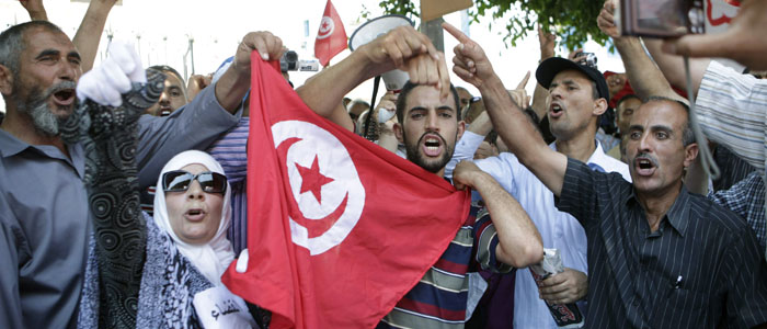 People shout slogans and wave flags during a protest against corruption in the judiciary system outside a court in Tunis