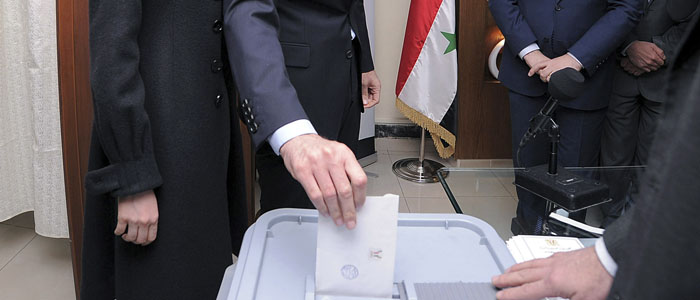 Syria's President Bashar al-Assad and his wife Asma vote during a referendum on a new constitution at a polling station in a Syrian TV station building in Damascus
