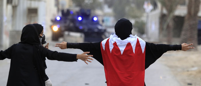 A female anti-government protester wearing a Bahraini flag confronts the riot police by standing in the middle of the road during clashes in the district of Sitra