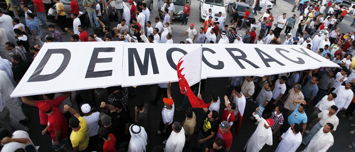 Protesters carry a large banner reading: ''Democracy'' as they participate in an anti-government protest in Budaiya highway