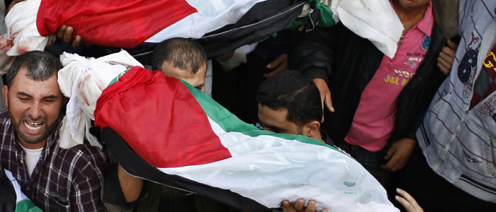 Palestinians carry the bodies of four siblings out of a hospital morgue in Gaza City