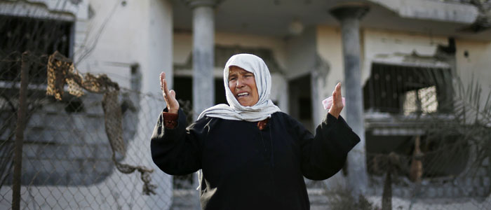A Palestinian woman cries in front of a house damaged in an Israeli air strike in Beit Hanoun in the northern Gaza Strip