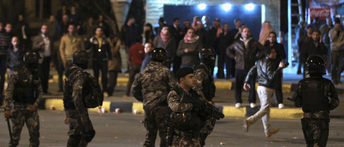 Jordanian gendarmerie policemen stand guard as protesters take part during a demonstration following an announcement that Jordan would raise fuel prices, including a hike on cooking gas, in Amman