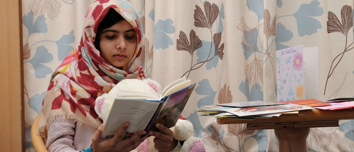 Pakistani schoolgirl Malala reads a book as she recuperates at the The Queen Elizabeth Hospital in Birmingham