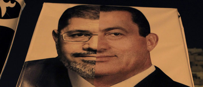 An Egyptian holds a banner against President Mohammed Morsi, comparing him with Hosni Mubarak, in Cairo