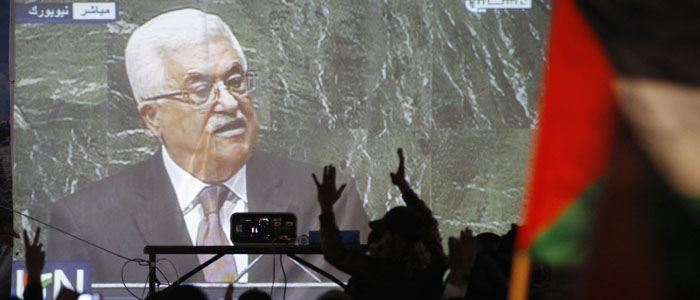 Palestinians take part in a rally while the speech of Palestinian President Mahmoud Abbas is projected in the West Bank city of Ramallah