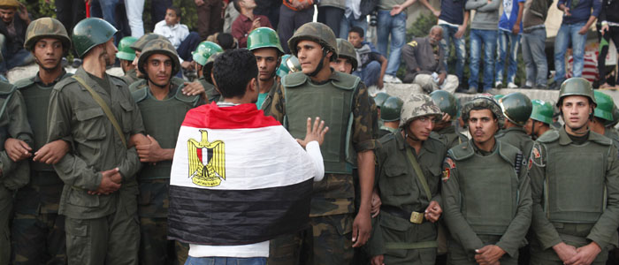 An anti-Mursi protester talks to soldiers standing guard outside the Egyptian presidential palace in Cairo
