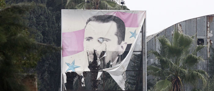 A torn poster of Syria's President Bashar al-Assad is seen at the entrance of a factory in Ouwayjah village in Aleppo