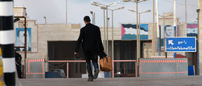 A man walks into the Syrian border after the road was blocked by Lebanese protesters at Arida town in northern Lebanon