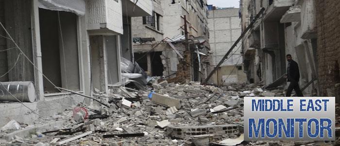 A man walks near damaged buildings in Erbeen