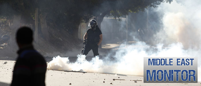 A policeman is seen through tear gas thrown back at him by protesters during clashes in Alexandria