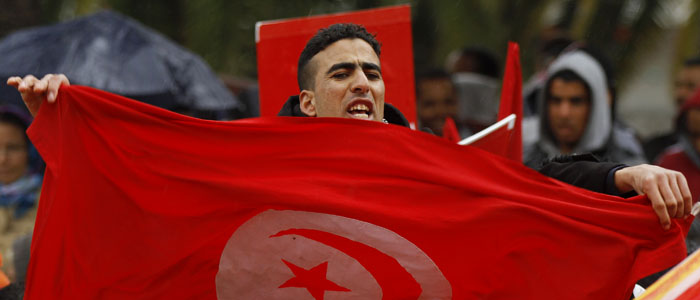 Demonstrator holds Tunisian flag as he joins others to protest outside the parliament in Tunis