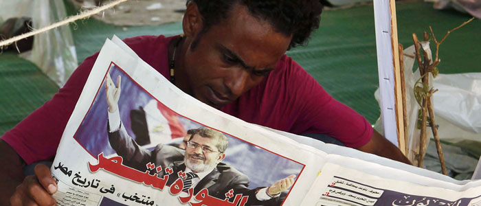 A protester reads a newspaper bearing a photo of President-elect Mohamed Mursi during a sit in at Tahrir square in Cairo