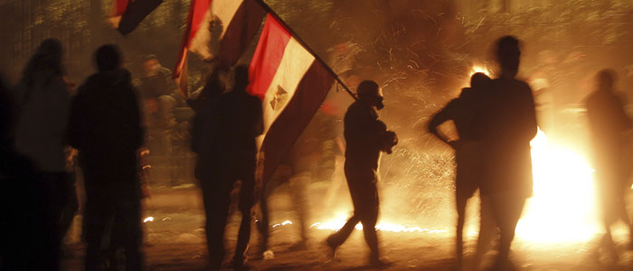 Protester opposing Egyptian President Mursi carries national flags during clashes in Cairo