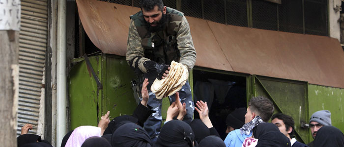 A member of the Free Syrian Army gives bread to people in Aleppo