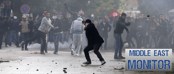 Protesters throw stones during clashes with riot police near the Interior Ministry in Tunis
