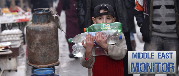 A boy carries bottles of water in Bustan al-Qaser, Aleppo