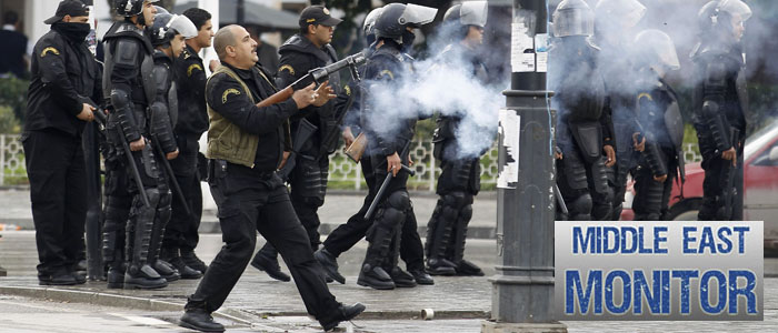 Police officer fires teargas to break up a protest during a demonstration in Tunis