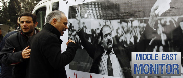 A man cries next to a poster with an image of Chokri Belaid, a prominent Tunisian opposition politician who was shot dead, in Tunis