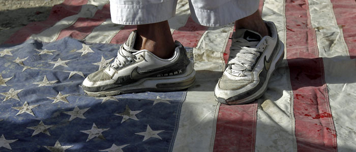 An Afghan protester steps on a U.S. flag during a demonstration in Kabul,