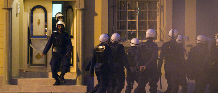 Police walk out of a home, which they raided, during clashes with anti-government protesters in Jidhafs, a suburb of Manama