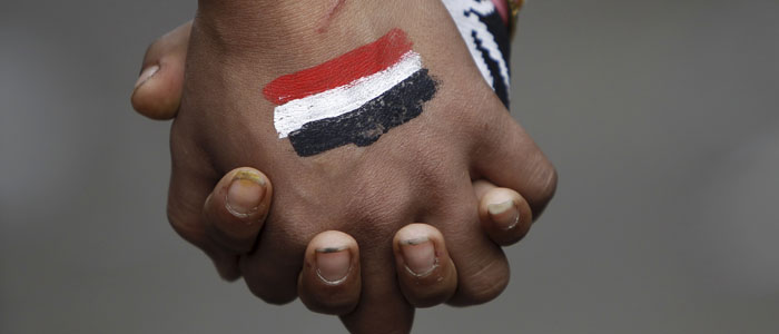 Anti-Mursi protesters, who want a peaceful demonstration, join hands as they try to stop clashes and rock-throwing at riot police along a road which leads to the U.S. embassy, near Tahrir Square in Cairo