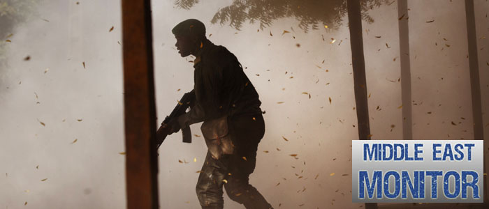 A Malian soldier takes cover amidst dust after a rocket propelled grenade was fired by his comrades in Gao