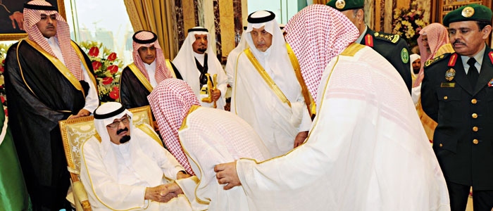 Saudi King Abdullah bin Abdulaziz Al Saud is greeted after attending prayers on the first day of Eid al-Fitr at Al-Safa Palace in Mecca