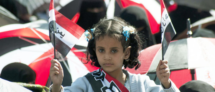 A girl holding national flags takes part in a rally by protesters demanding the trial of Yemen's outgoing President Ali Abdullah Saleh in Sanaa