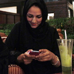 FILE - A Saudi woman checks her smartphone at a coffee shop in Jeddah, Saudi Arabia. (AP)