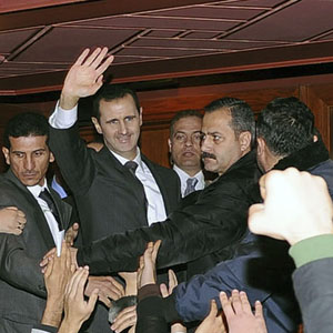 President Bashar al-Assad (C) waves to his supporters after speaking at the Opera House in Damascus January 6, 2013. (Reuters/SANA handout)