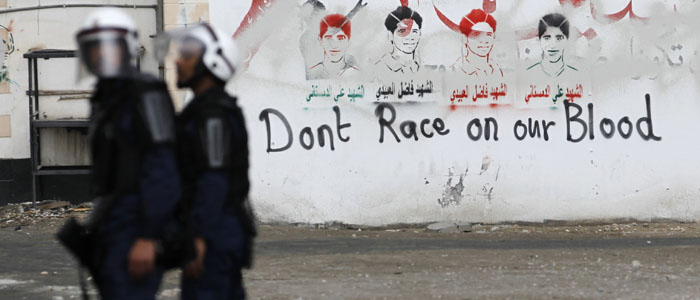 Riot police officers stand near an anti-Formula One graffiti during an anti-government protest in the village of Diraz