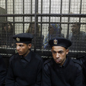 Egyptian civil society activists accused of working for unlicensed NGOs and receiving funds from questionable sources are seen caged under guard at their trial in Cairo February 26, 2012. (Reuters)