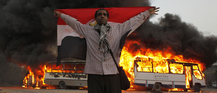 An anti-Morsi protester stands with the national flag in front of burning Muslim Brotherhood buses in Cairo March 22, 2013. (Reuters).