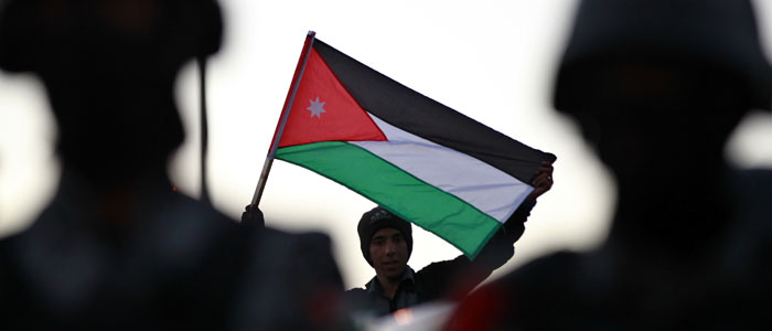 A government supporter holds a Jordanian national flag at a rally in Amman. (Reuters file)